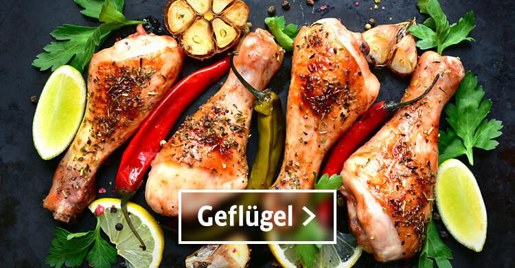 Gefluegel, Hühnerschenkel auf einer Schieferplatte mit Chili-Schoten, gegartem Knoblauchzehen, frischen Zitronen und Petersilie