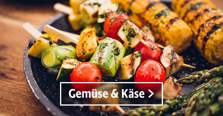 Gemuse und Kaese, drei gegrillte Spiesse mit Lach, Zucchini und Tomaten auf einem Teller. Daneben befinden sich zwei gegrillte Maiskolben und etwas grüner Spargel.